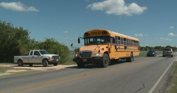 San Marcos CISD bus approaching a bus stop_350131