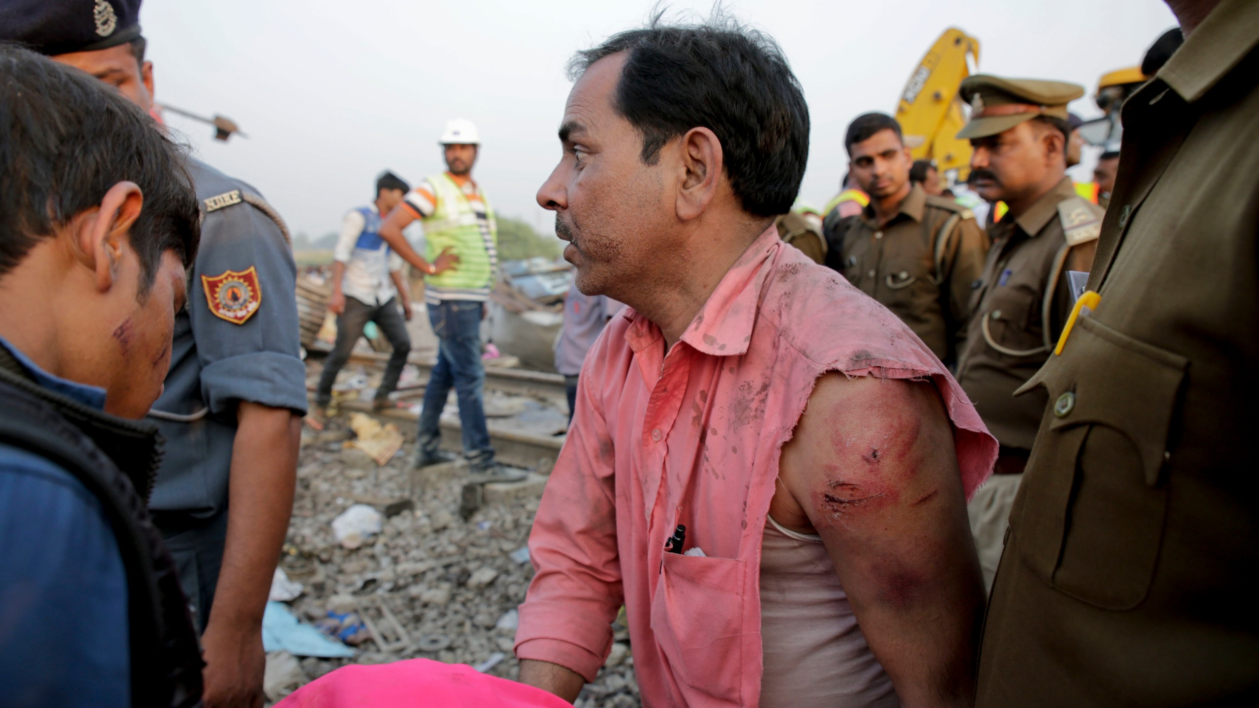 An injured survivor looks for a missing member of his team after 14 coaches of an overnight passenger train rolled off the track near Pukhrayan_377040