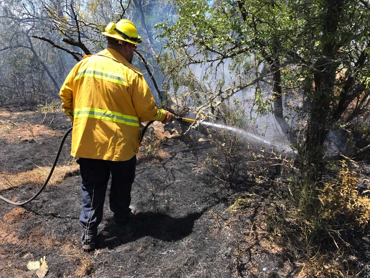 Crews mopping up a brush fire on Synergy Drive near Bastrop, Texas on July 5, 2017_501439