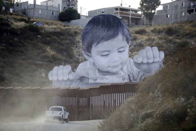 A photo of a giant toddler stands in Mexico and peers over a steel wall dividing the country from the United States._541787