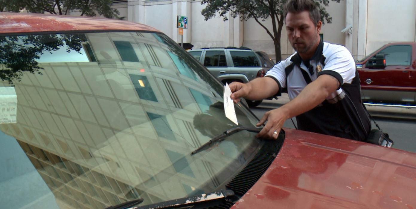 Austin Transportation Department Enforcement Supervisor Lyndon Meris issuing a parking ticket. (KXAN Photo)