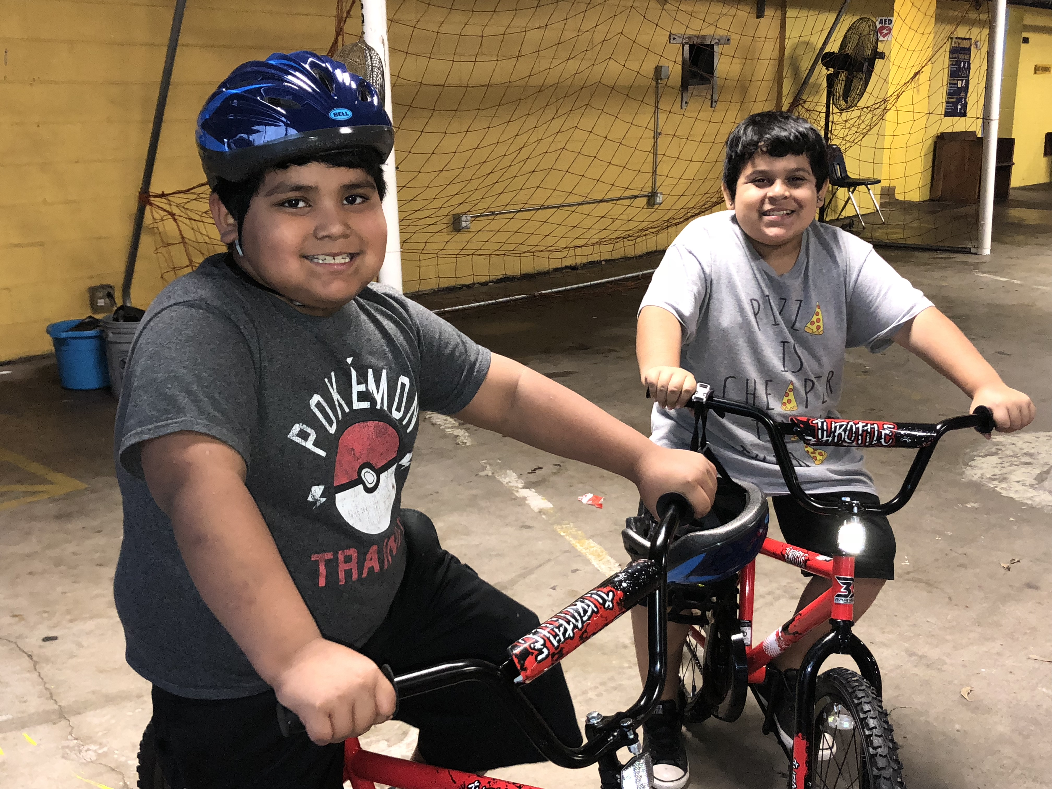 Two children with their new bikes, courtesy of the Hispanic Contractor's Association and the Austin Police Department. (KXAN Photo/Julie Karam)