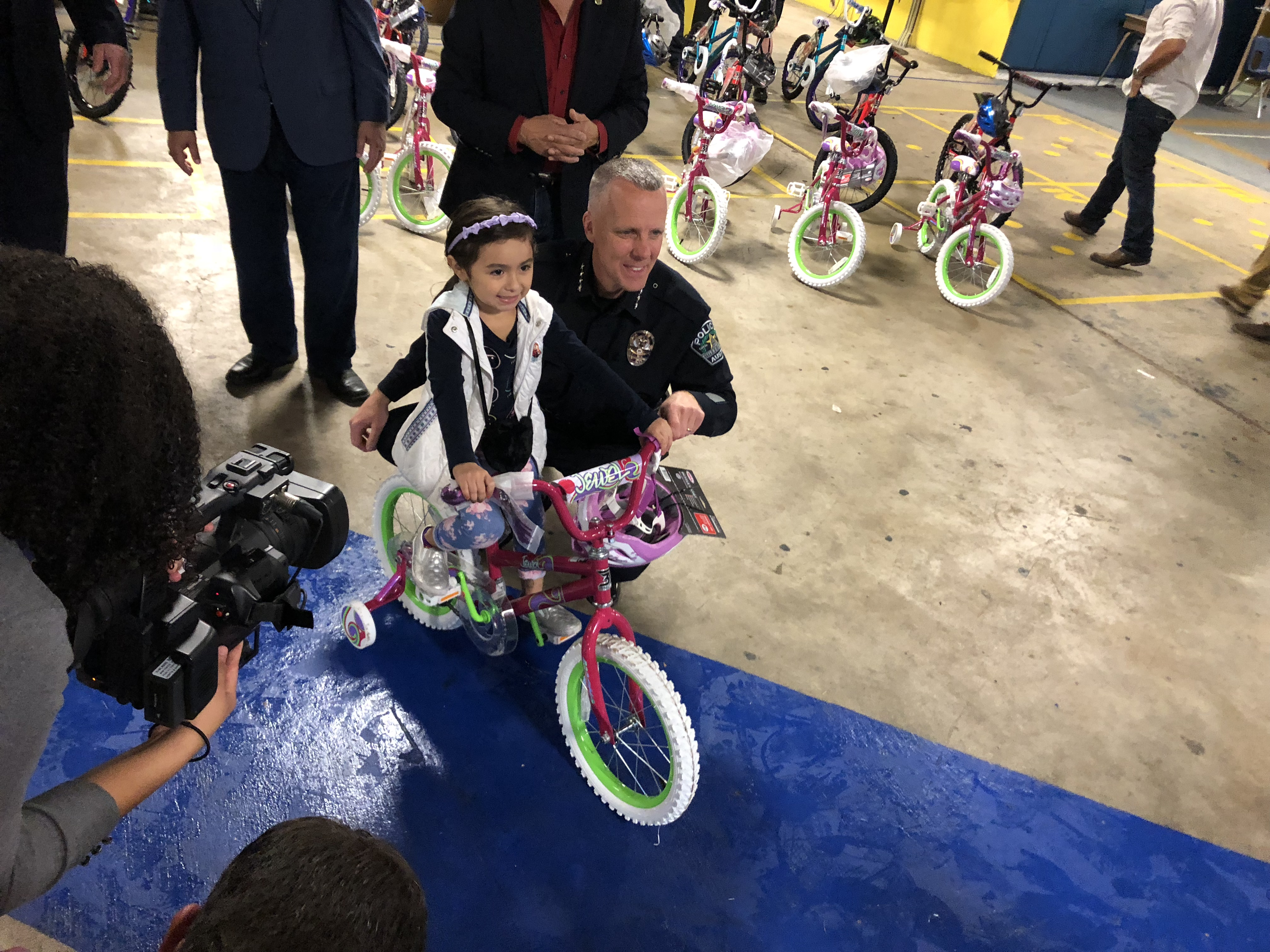 A little girl with her new bike and APD Chief Brian Manley (KXAN Photo/Julie Karam)