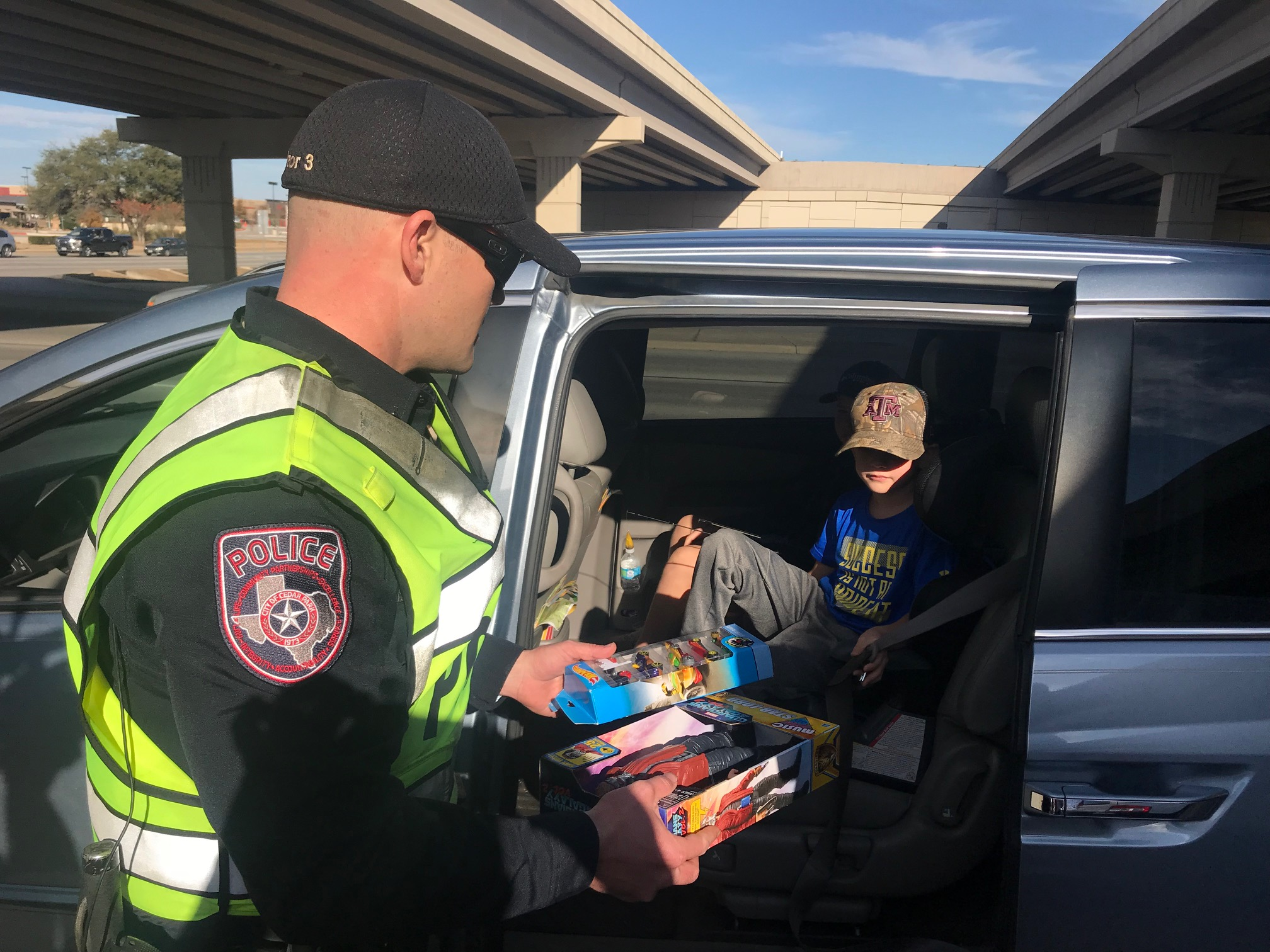 """Cedar Park police officer hands out toys to a child during a holiday """"traffic"""" stop. (KXAN Photo/Frank Martinez)"""