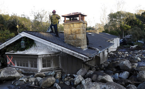 A firefighter stands on the roof of a house submerged in mud and rocks Wednesday, Jan. 10, 2018, in Montecito, Calif. Anxious family members awaited word on loved ones Wednesday as rescue crews searched grimy debris and ruins for more than a dozen...