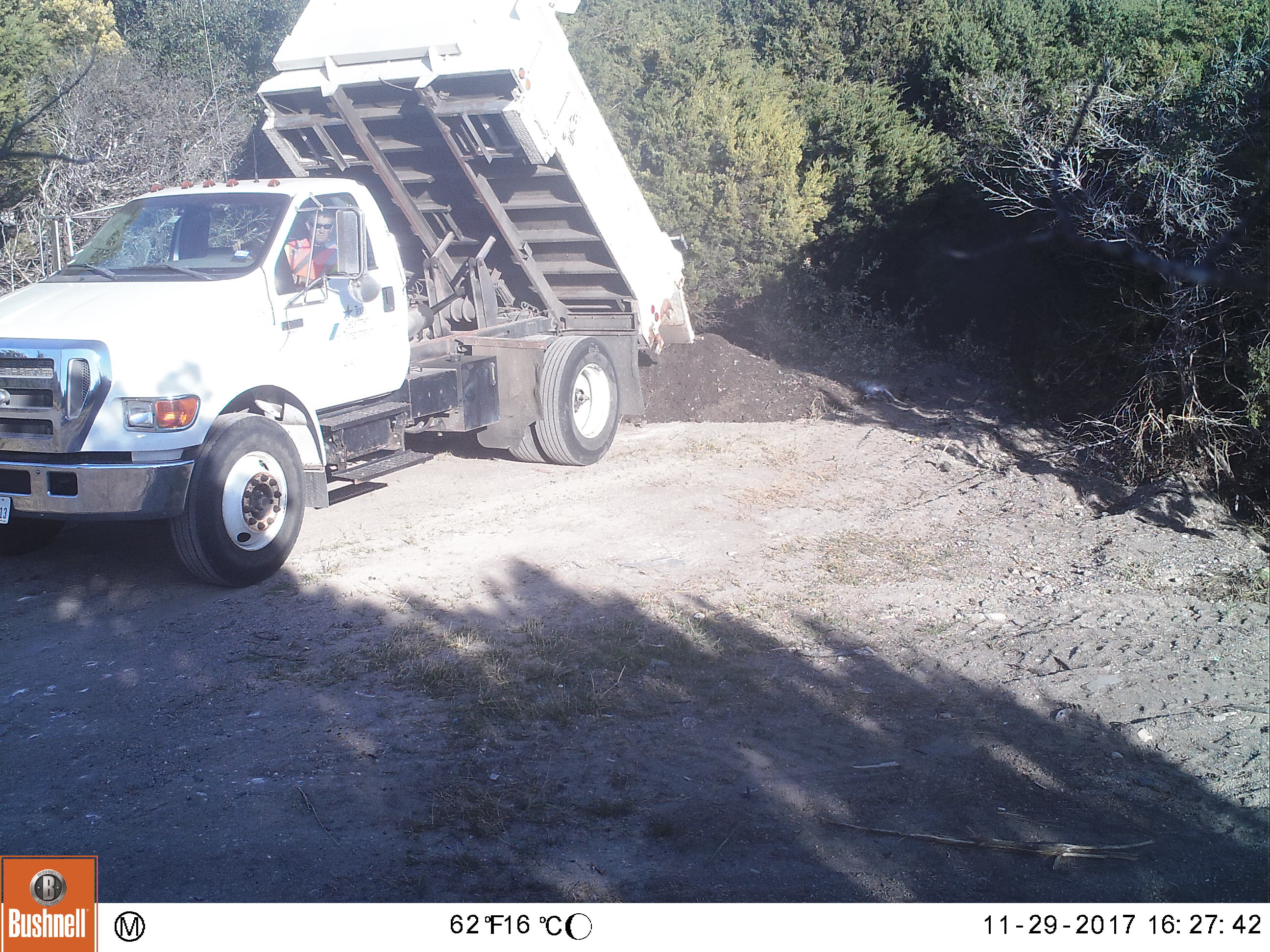 TxDOT truck  dumping a load of dirt and garbage over a dead deer and tire on Nov. 17, 2017. KXAN later checked the pile of debris and found luggage, plastics and random trash in it. (KXAN Photo)