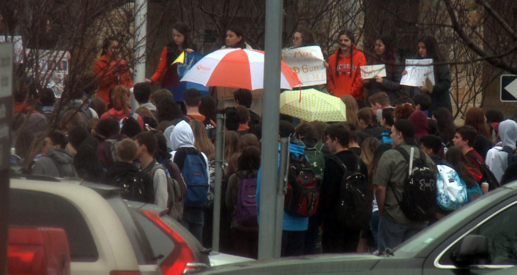 Students from Dripping Springs High School stand in the rain protesting gun violence in schools. (KXAN Photo)