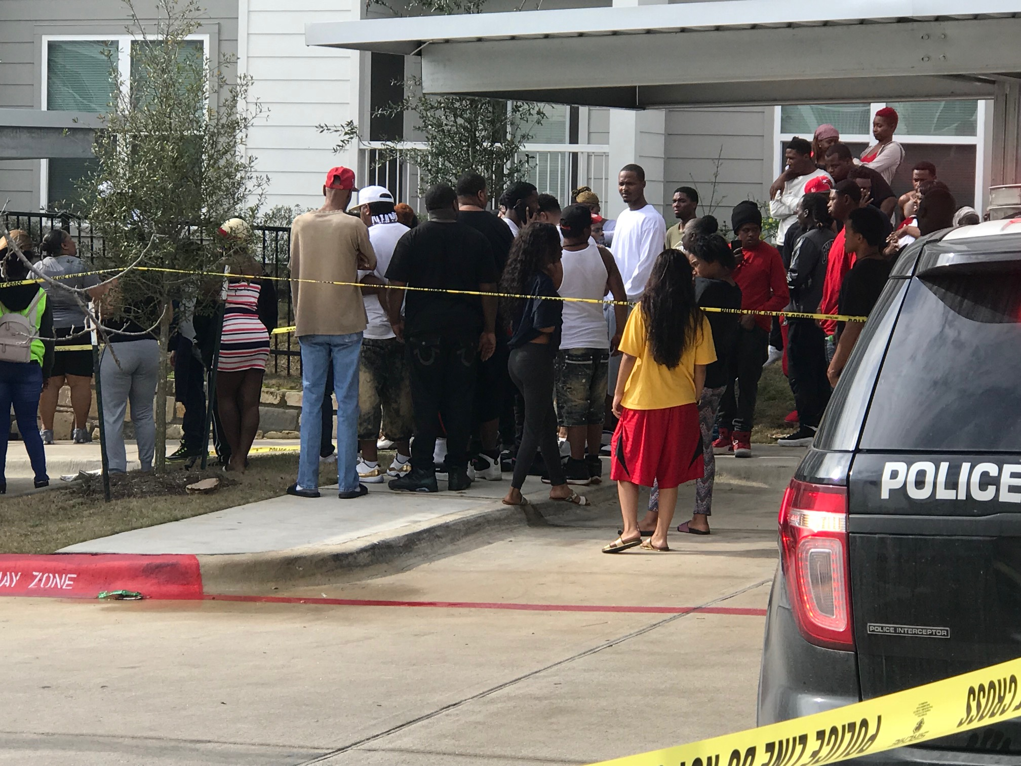 People gather outside the Reserve at Springdale Apartments where a man died of gunshot wounds March 5, 2018 (KXAN Photo/Frank Martinez)