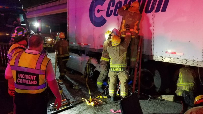 A car trapped after crashing into a semi truck trailer on the lower deck of Interstate 35 on July 15, 2018
