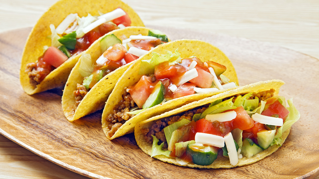 Four tacos laying on a plate