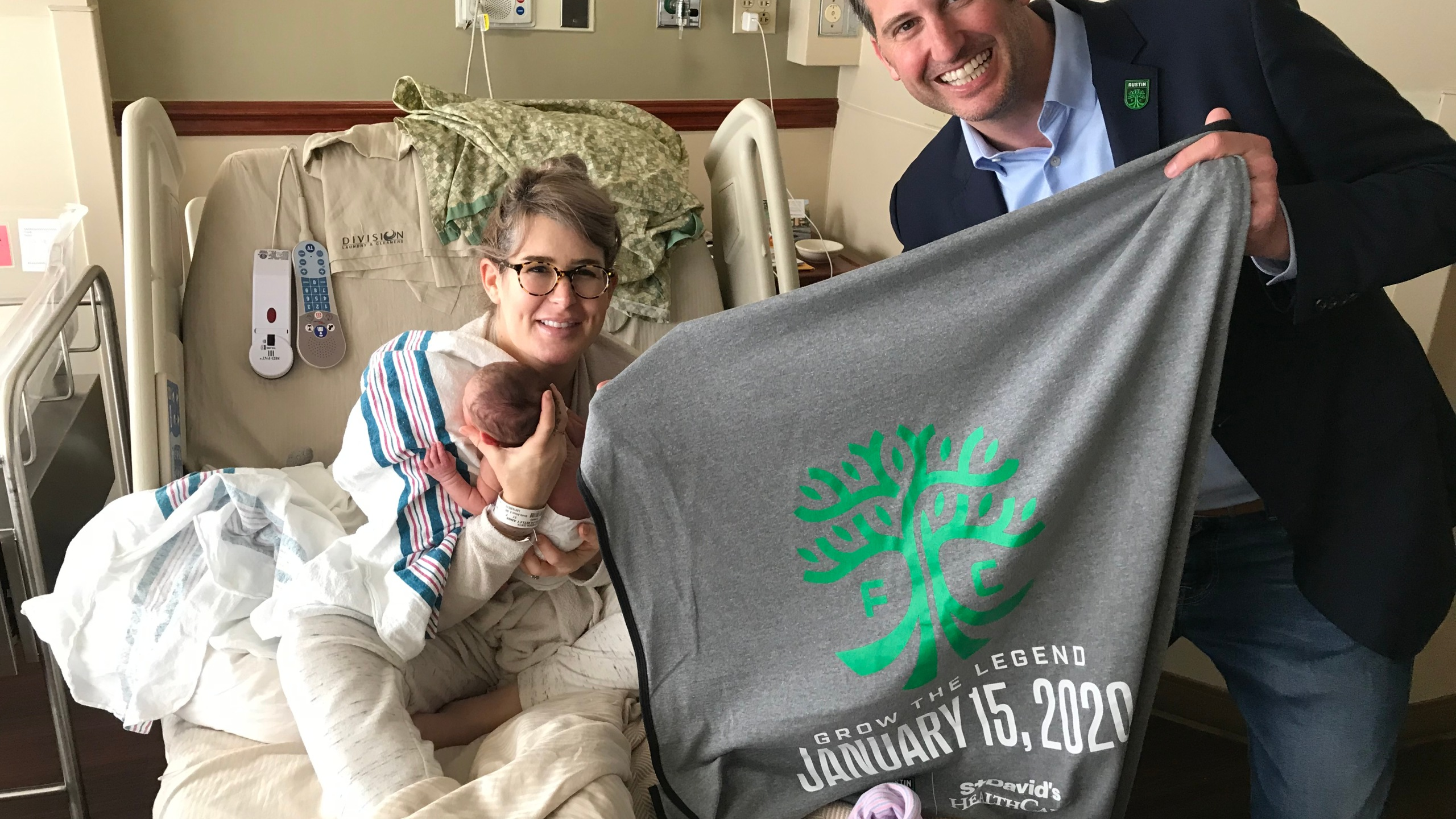 Austin FC president gifts newborns with official team baby blankets.