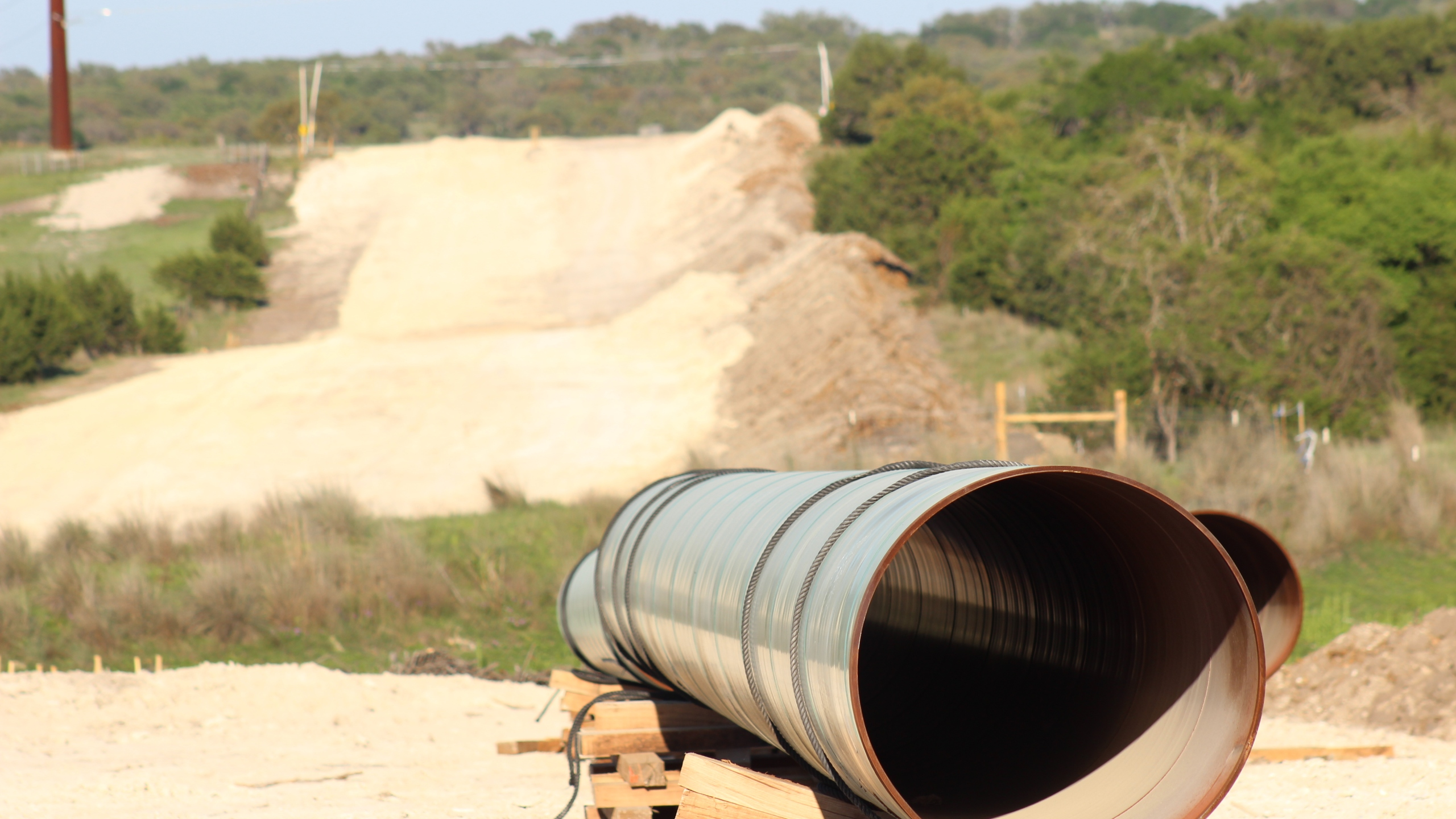 On April 15, 2020, pipe segments sat along this stretch of what will become the trench for Kinder Morgan's Permian Highway Pipeline in Gillespie County. (KXAN Photo/Jody Barr)