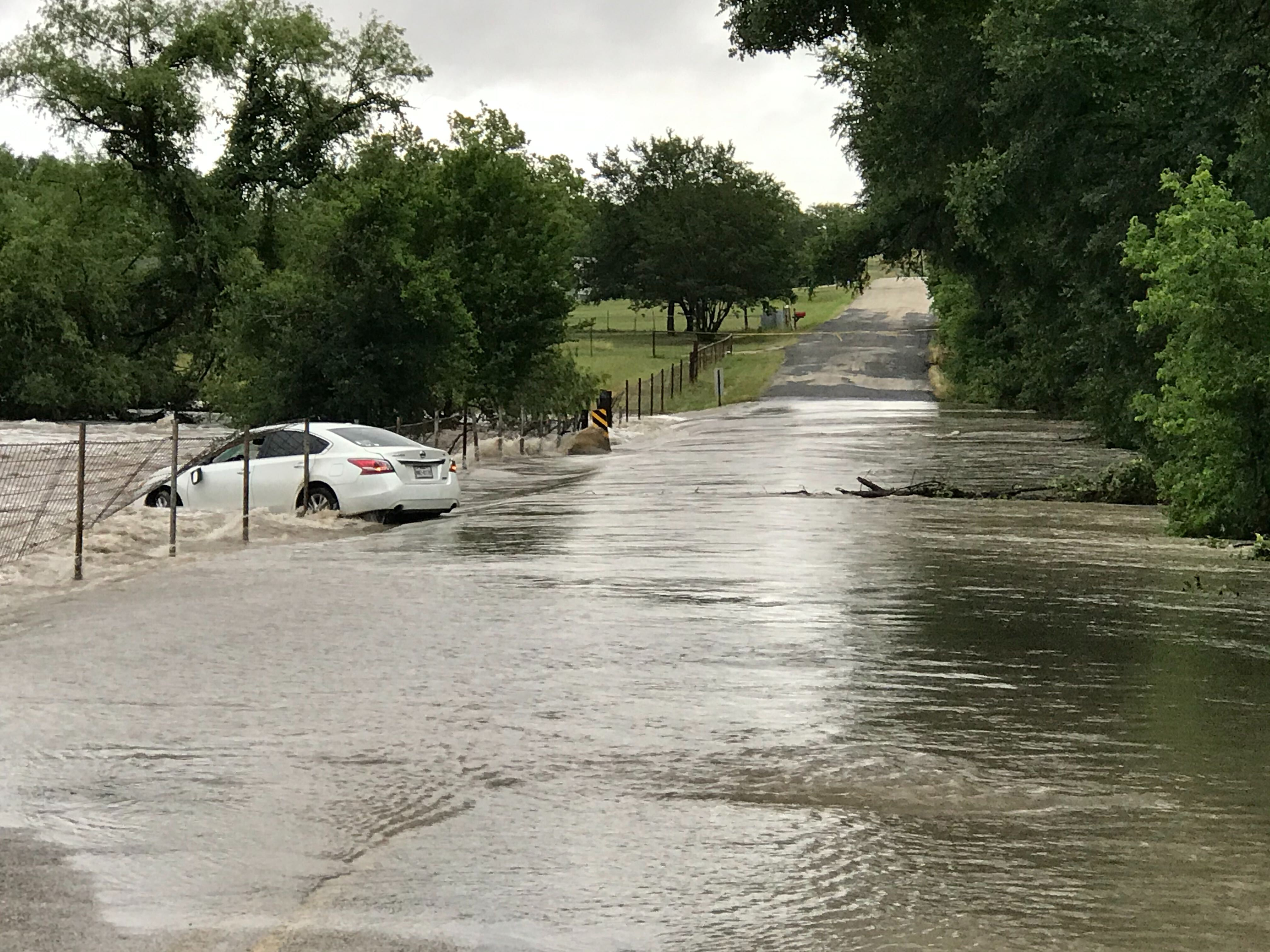 A car was swept into the water on Grist Mill Road in Hays County May 12, 2020 (KXAN Photo/Tim Holcomb)