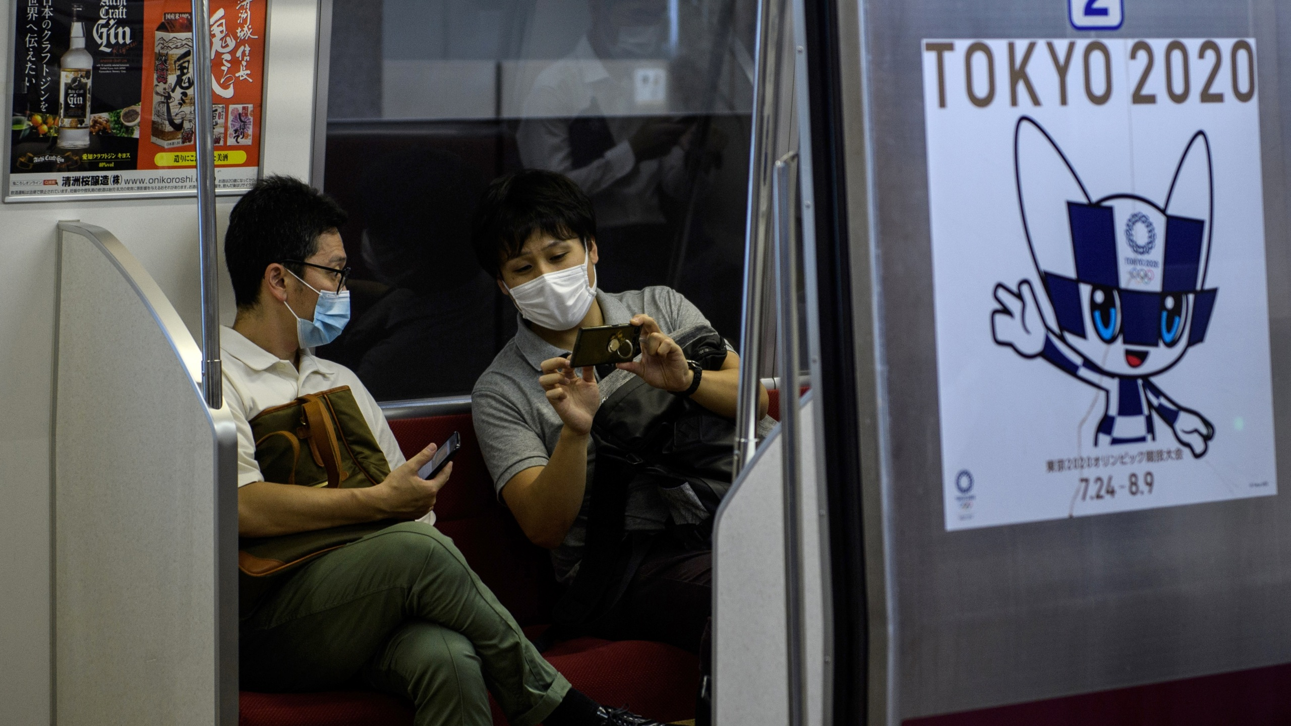 This picture taken on July 13, 2020 shows passengers talking inside a train near an advertisement (R) for the Tokyo 2020 Olympic Games in Tokyo. (Photo by Philip FONG / AFP)