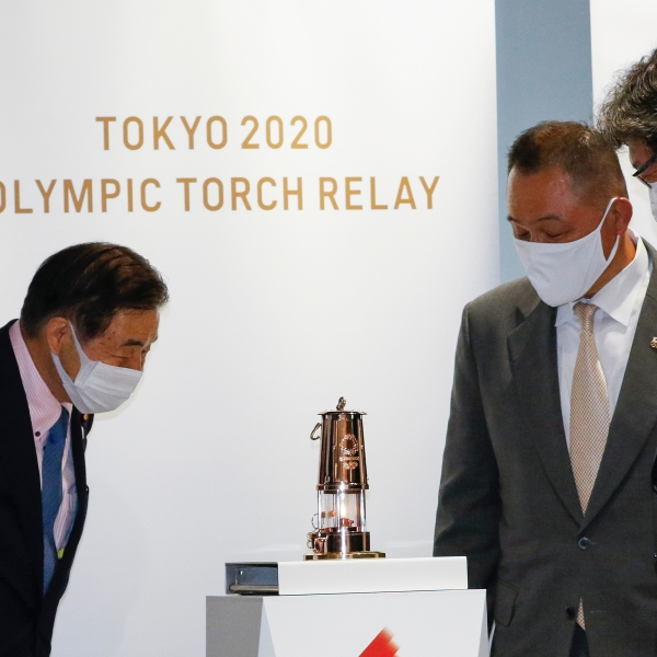 Representatives of the Tokyo Organizing Committee of the Olympic and Paralympic Games (Tokyo 2020) and the Japanese Olympic Committee look at the Olympic Flame after the display ceremony at the Olympic Museum in Tokyo Monday, Aug. 31, 2020. The Olympic flame is going on display in Tokyo, just a short walk from the new National Stadium where it was supposed to be burning a month ago. (Rodrigo Reyes Marin/Pool Photo via AP)