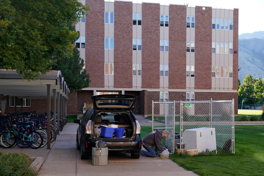 Ryan Dupont, Utah State University Professor of Civil & Environmental Engineering, collects sewage samples from the dorms at Utah State University Wednesday, Sept. 2, 2020, in Logan, Utah. About 300 students are quarantined to their rooms this week, but not because anyone got sick or tested positive. Instead, the warning bells came from the sewage. Colleges around the country are monitoring wastewater in hopes of stopping coronavirus outbreaks before they get out of hand. Utah State became at least the second school to quarantine hundreds of students after sewage tests detected the virus. (AP Photo/Rick Bowmer)