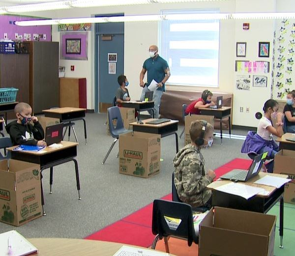 Children participate in remote learning with assistance from a district staff member in a learning pod (KDVR Photo/ Lori Jane Gliha)