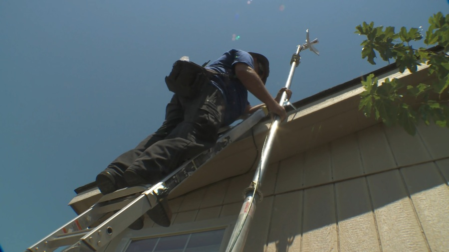 A technician works to install an antenna on a home  (KXAN Photo/Chris Nelson)
