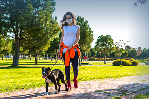 A woman walks her dog (Texas Mutual Sponsored Content Photo)