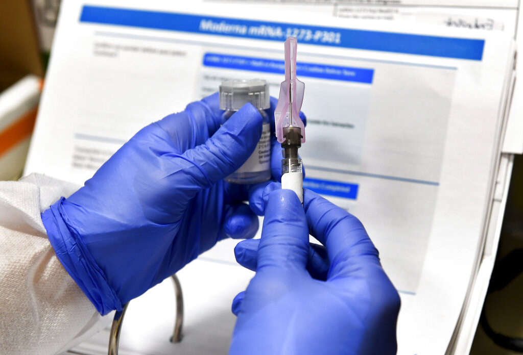 Nurse Kathe Olmstead prepares a shot that is part of a possible COVID-19 vaccine, developed by the National Institutes of Health and Moderna Inc., in Binghamton, N.Y. in July. (AP Photo/Hans Pennink, File)