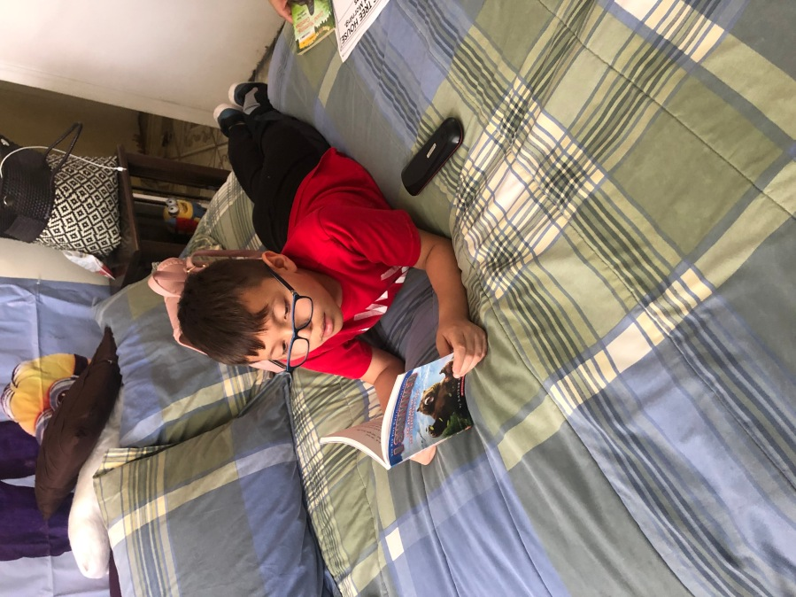 Alexander Luevano reads on his family's bed (Courtesy Luevano family)