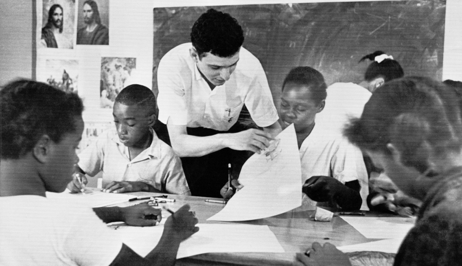 "In this Aug. 23, 1964 file photo, Bruce Solomon, of the Brooklyn borough of New York, teaches a class for young black students about arts, African American history and rights at a ""Freedom School"" in Jackson, Miss. Solomon was one of hundreds of volunteers in the ""Mississippi Summer Project."" The classes throughout the state were set up by the volunteer workers in churches, homes and other buildings to encourage African Americans to register to vote during the long hot summer. (AP Photo/BH, File)"