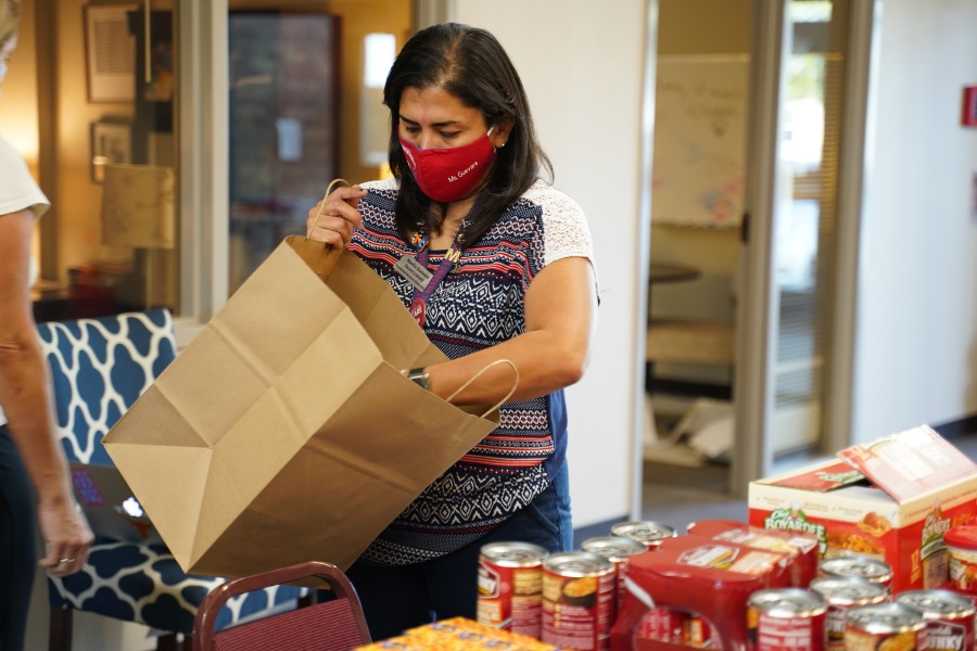 A woman helps back a bag full of food to be distributed through the Manor Schoolhouse Foundation's program (Courtesy Manor Schoolhouse Foundation)