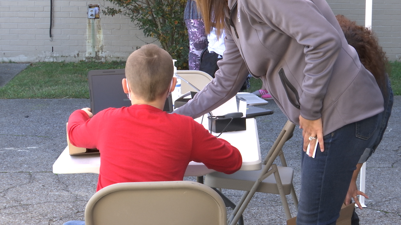 A worker helps an English Learner log into his laptop in Nashville (WKRN Photo)