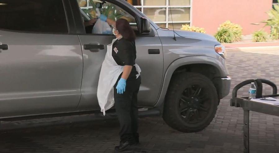 A McAllen ISD food worker hands a meal to someone in a car (KVEO Photo)