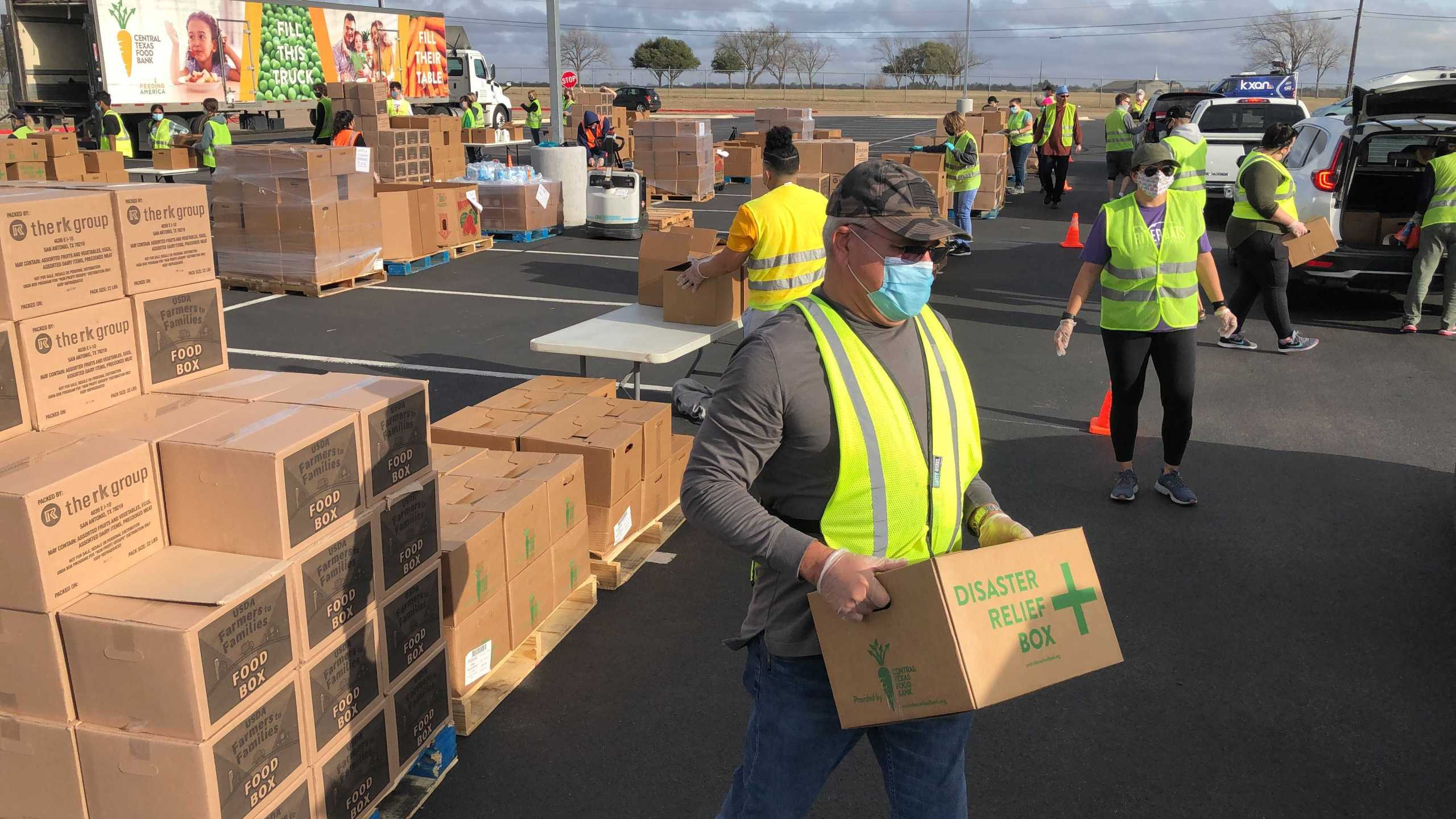 Teams of volunteers from the Central Texas Food Bank loads up cars during a drive-thru food distribution Tuesday at Del Valle High School.