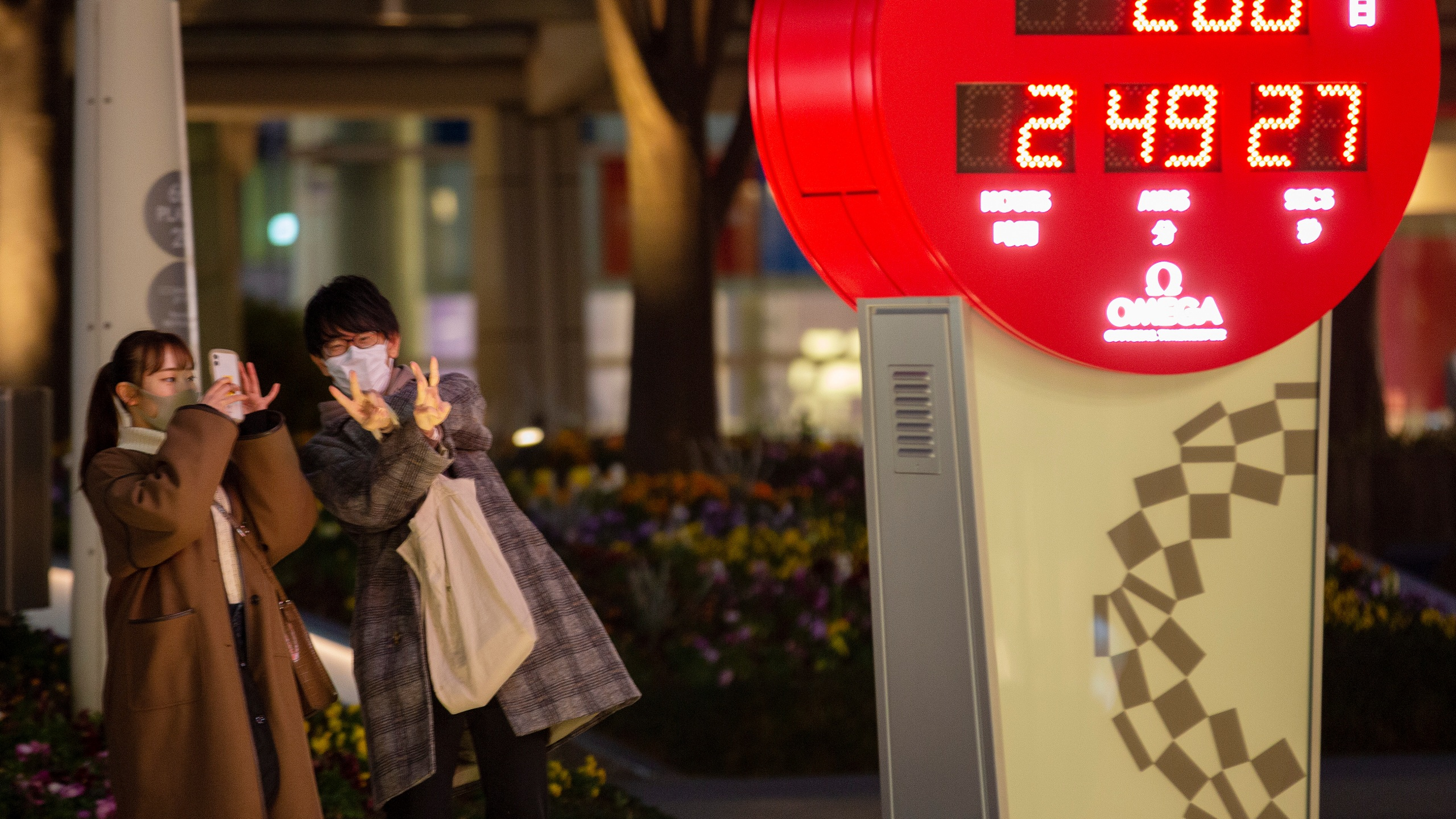 People wearing face masks walk by a countdown calendar showing 200 days to the opening ceremony of the Tokyo 2020 Olympics Monday, Jan. 4, 2021, in Tokyo. The countdown clock for the postponed Tokyo Olympics hit 200 days to go on Monday. Also on Monday, Japanese Prime Minister Yoshihide Suga said he would consider calling a state of emergency as new coronavirus cases surge to record numbers in Tokyo and neighboring prefectures. (AP Photo/Kiichiro Sato)