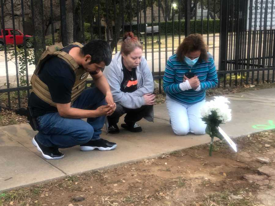 Family and a stranger pray at the site on Wickersham Lane where police shot and killed Alexander Gonzales Jan. 5, 2020 (KXAN Photo/Frank Martinez)