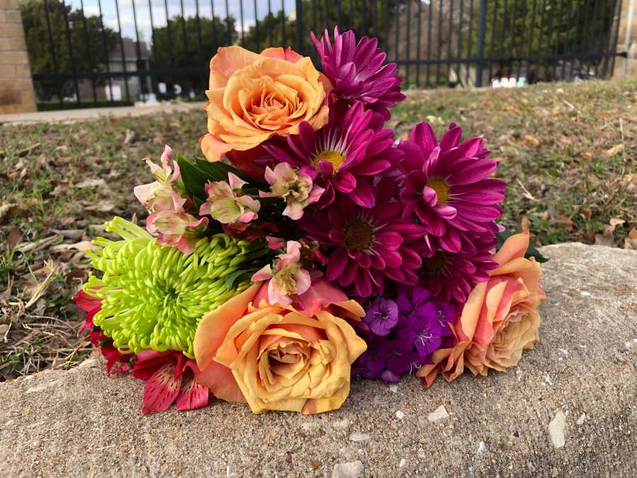 Fresh flowers sit on Wickersham Lane where police shot a man Jan. 5, 2020 (KXAN Photo/Frank Martinez)