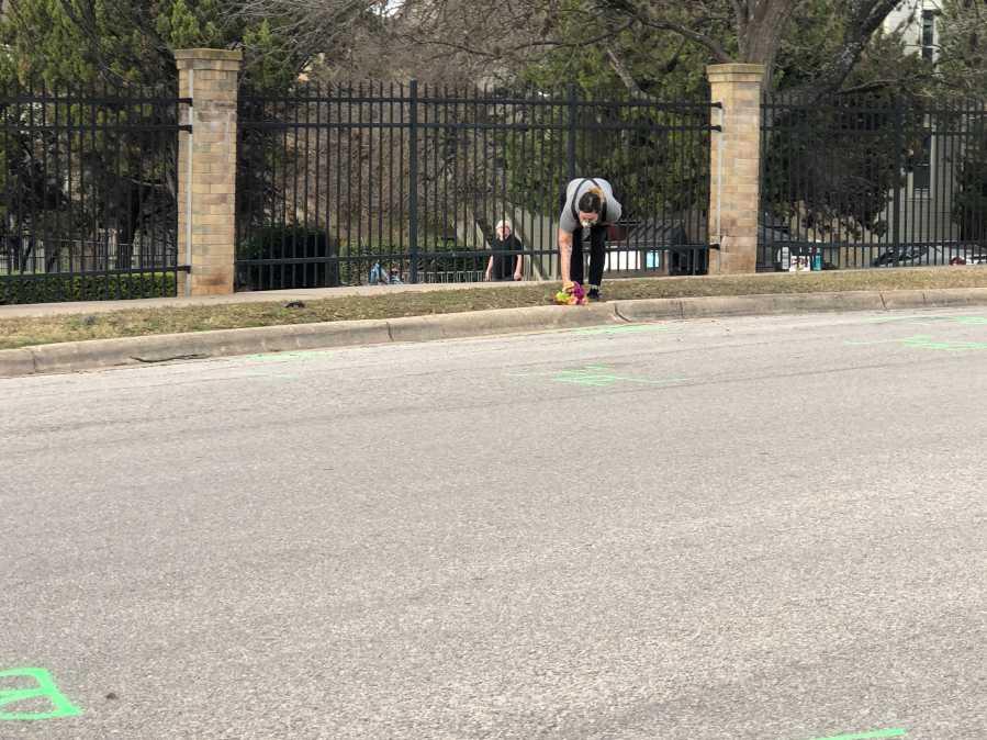 A woman drops off fresh flowers on Wickersham Lane where police shot a man Jan. 5, 2020 (KXAN Photo/Frank Martinez)