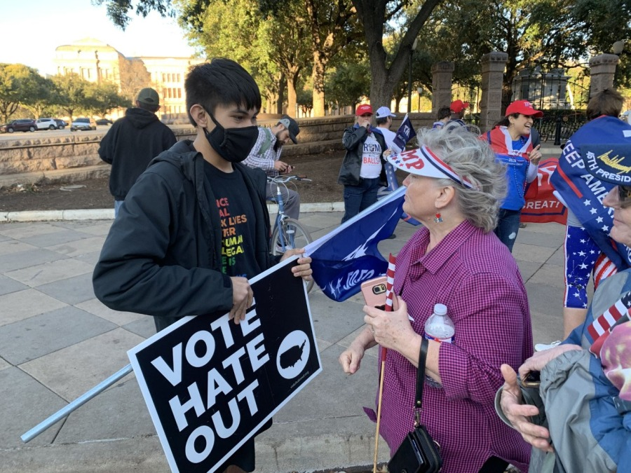Felix Luna holds a Biden flag and speaks with Trump supporters who protested at the Texas State Capitol Jan. 6 (KXAN Photo/Avery Travis)