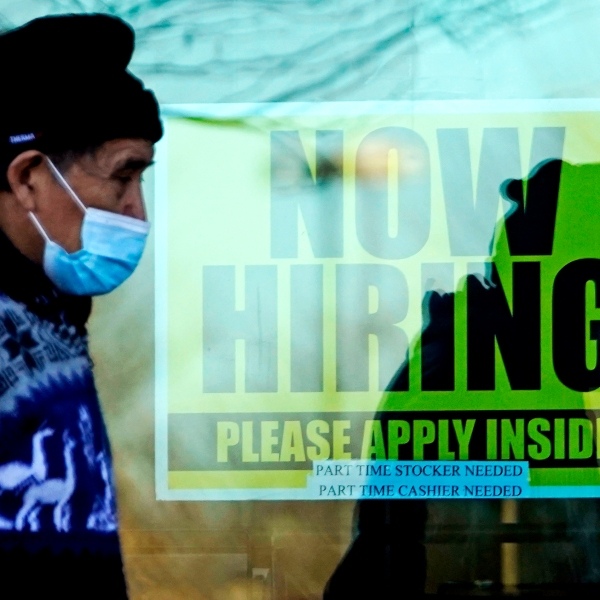 In this Nov. 28, 2020 file photo, a shopper wears a face mask and he walks past a store displaying a hiring sign in Wheeling, Ill. The number of Americans seeking unemployment benefits fell sharply last week but remained high by historical standards. Applications for benefits declined 111,000 from the previous week to a seasonally adjusted 730,000, the Labor Department said Thursday, Feb. 25. It is the lowest figure since late November. (AP Photo/Nam Y. Huh, File)