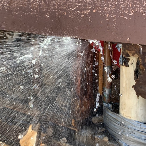 A broken pipe leaks out of a wall. (Source: Barrera Plumbing Services)
