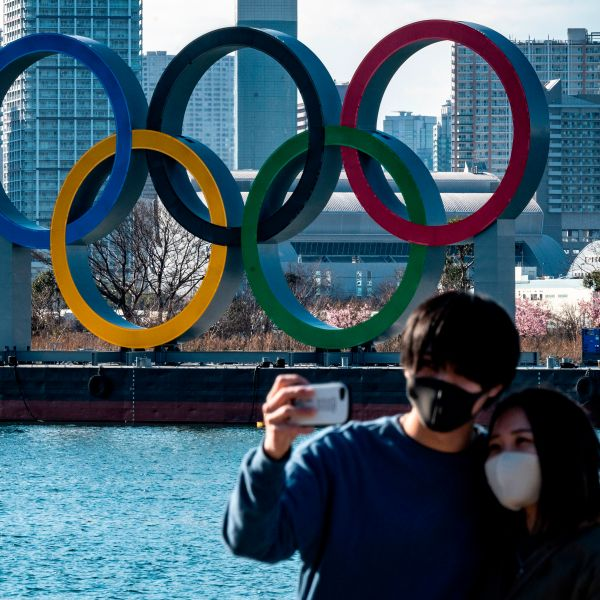 A couple pose for photos in front of the Olympic rings on display at the Odaiba waterfront in Tokyo on February 24, 2021. (Photo by Philip FONG / AFP) (Photo by PHILIP FONG/AFP via Getty Images)