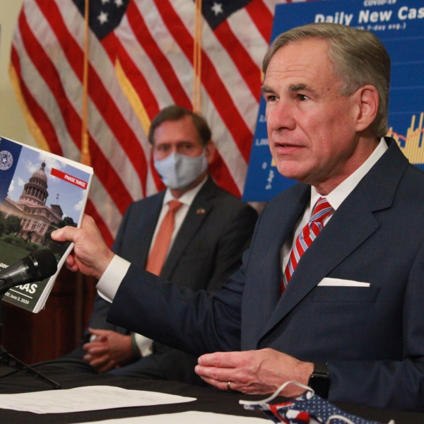 Governor Abbott, sitting behind a table, holds a booklet describing pandemic mitigation measures and business protocols. Behind him are 3 of his top advisors and charts showcasing COVID-19 data.