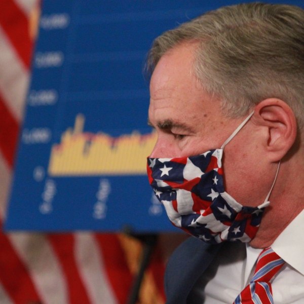 Governor Abbott wears Texas flag facemask sitting in front of chart of COVID-19 hospital data