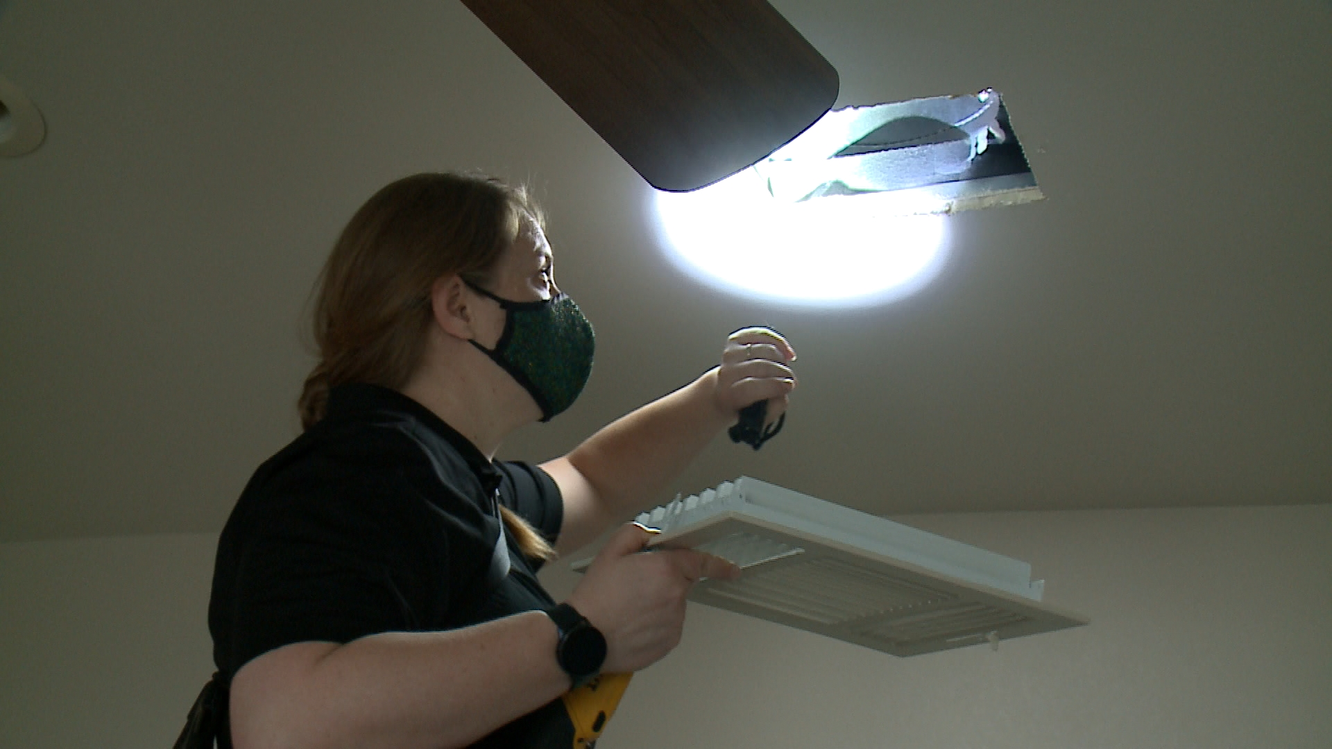A woman on a ladder shines a flashlight into a air vent in a home as part of a mold inspection