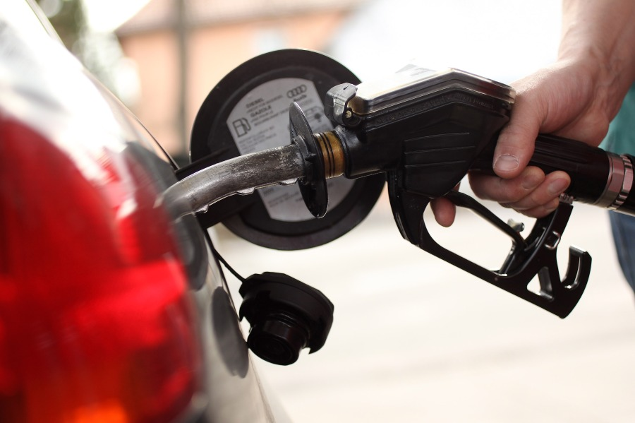 A driver pulls a gas pump from their car after filling up
