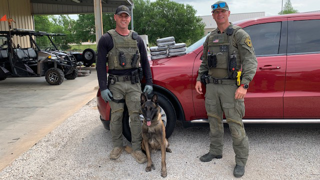 Fayette County Sheriff's Office Sgt. Randy Thumann, K9 Kolt and Investigator Dan Smith with the nearly 20 pounds of cocaine they seized during a Monday traffic stop on I-10. (Fayette County Sheriff's Office photo)