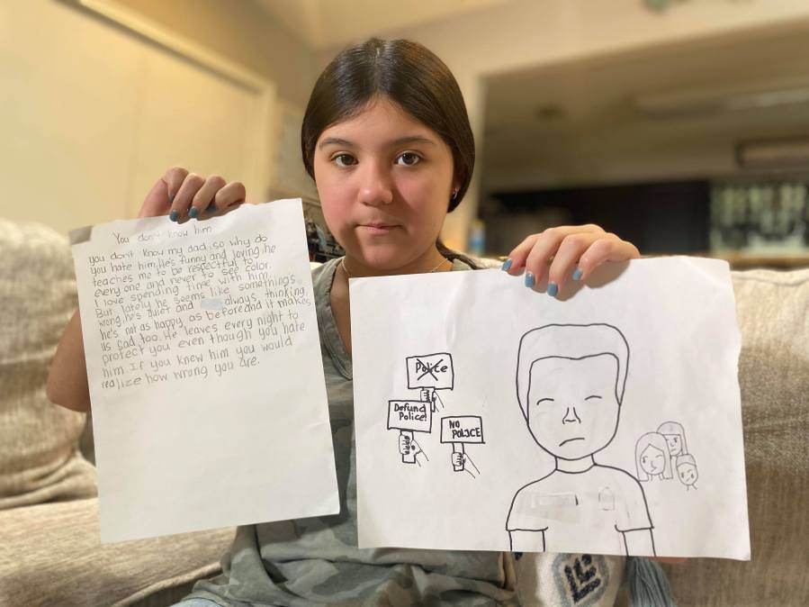 Chloe holds up her poem and a picture she drew of her dad