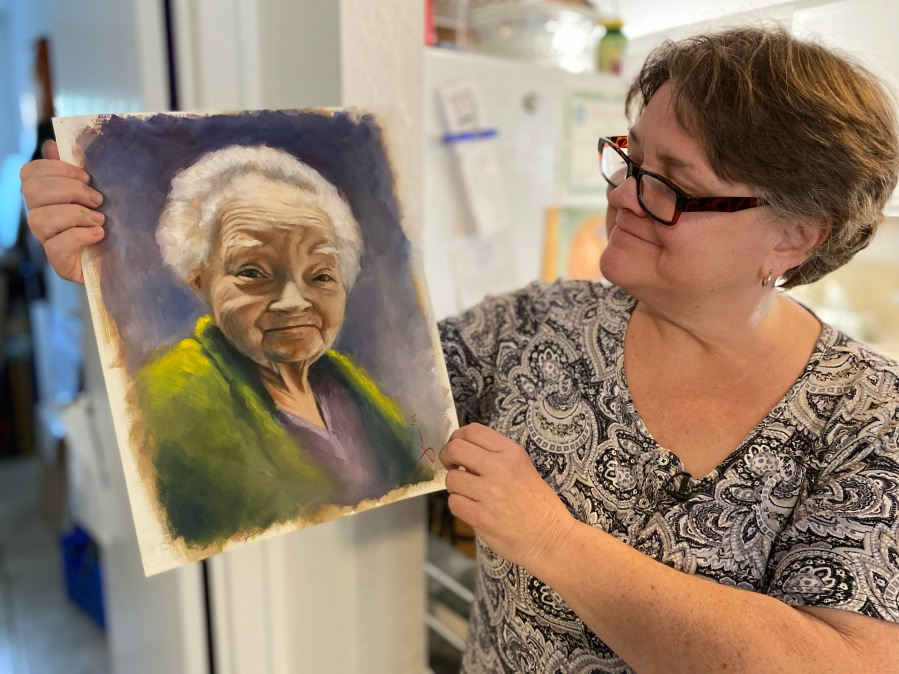 Jamie Canfield holds a portrait she painted of her mother who died in 2019. Canfield, who paints as a hobby, worked for the U.S. Census bureau until she was laid off in November 2020. (KXAN Photo/Jody Barr)
