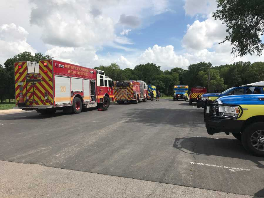 """Emergency crews are in southeast Austin after reports of an adult """"hanging on to a tree"""" in the middle of the creek, according to Austin-Travis County EMS. The adult is now out of the water and being moved to an ambulance. (KXAN Photo/Ed Zavala)"""