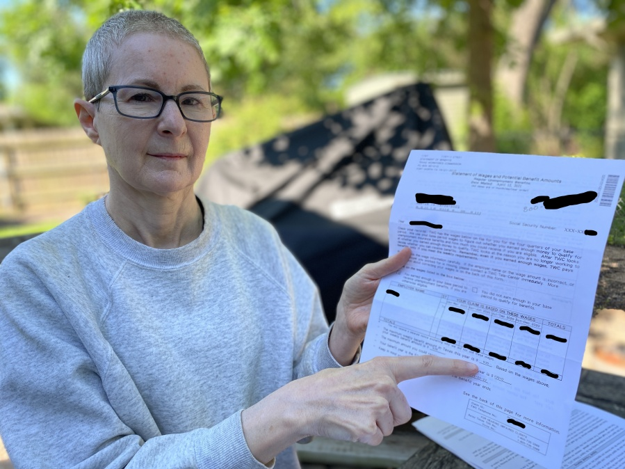 Lisa Martin shows the unemployment notice saying her husband would receive benefits of $535 each week. The TWC later told the Martins the claim filed in his name was fraudulent. (KXAN Photo/Jody Barr)