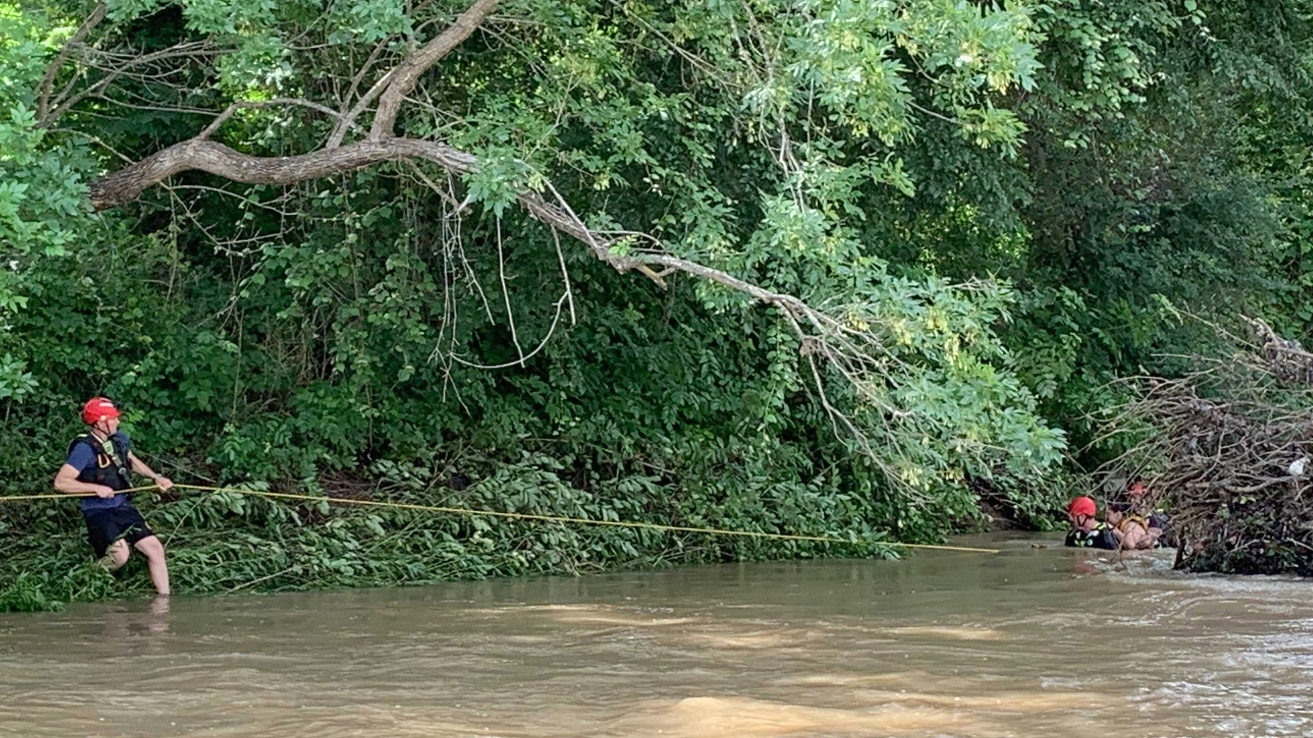 """Emergency crews are in southeast Austin after reports of an adult """"hanging on to a tree"""" in the middle of the creek, according to Austin-Travis County EMS. The adult is now out of the water and being moved to an ambulance. (Austin Fire Photo)"""