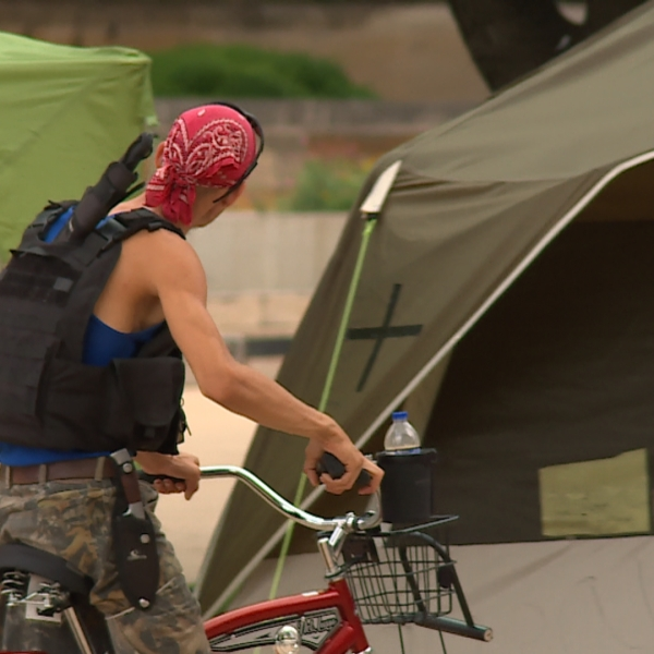 A man armed with knives rides a bike around the encampment around City Hall on Tuesday. The encampment has been in front of City Hall for weeks after the city's renewed camping ban, Proposition B, was passed by voters. (KXAN photo/Richie Bowes)