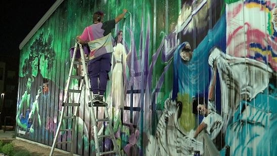 Artist painting mural outside Q2 stadium